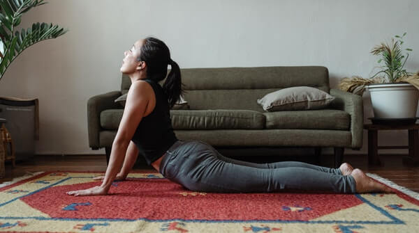 a woman practicing cobra pose or bhujangasana yoga at home. It stretches the chest cavity, shoulders and abdomen. Also strengthens the spine