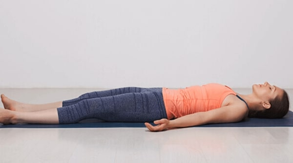 a woman is doing the Corpse pose also known as savasana to end her yoga session. Helps in overall relaxation of the body