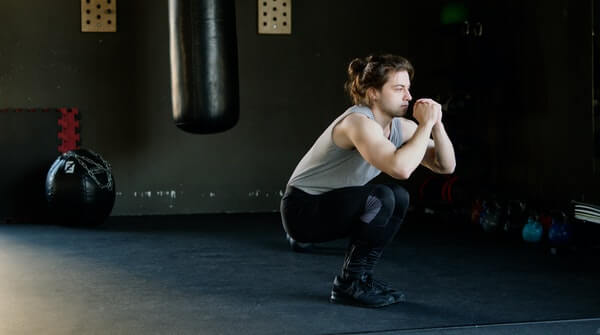 a man doing squats- a classic workout exercise to strengthen leg muscles