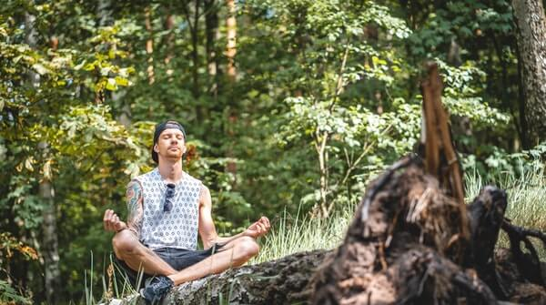 a man doing meditation outdoors to experience the nature with mindfulness