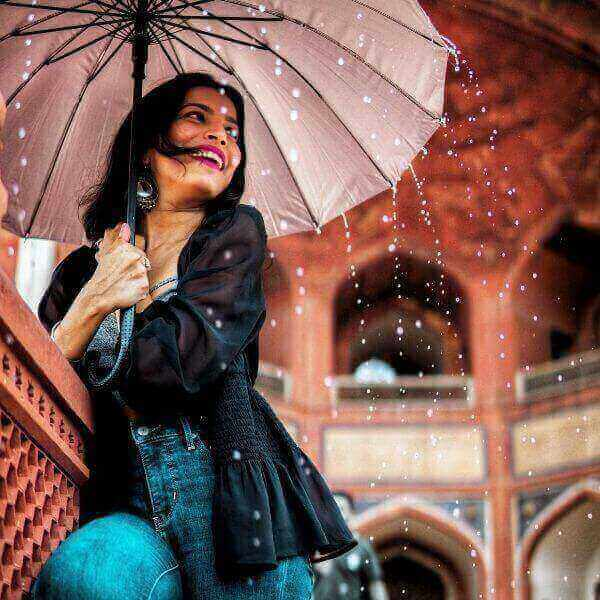 Girl wearing an apt outfit for rainy day. Holding an umbrella and smiling.