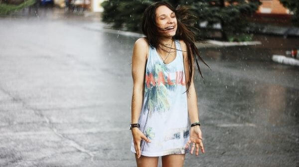 A girl is wearing rainy season attire and she is enjoying the rain very much.