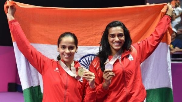 Saina and P.V. Sindhu posing together with the Indian flag after Nehwal beats her in the finals of the Australian Super Series