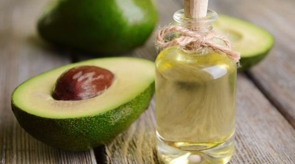 a flask of avocado massage oil with some some avocados near it.