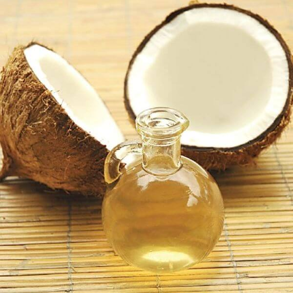 A flask of coconut massage oil with two halves of coconut.