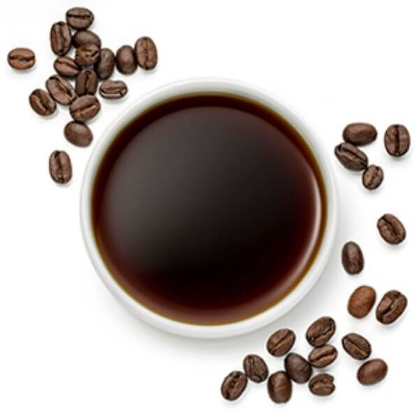 a cup of coffee seed oil with some coffee seeds around it.