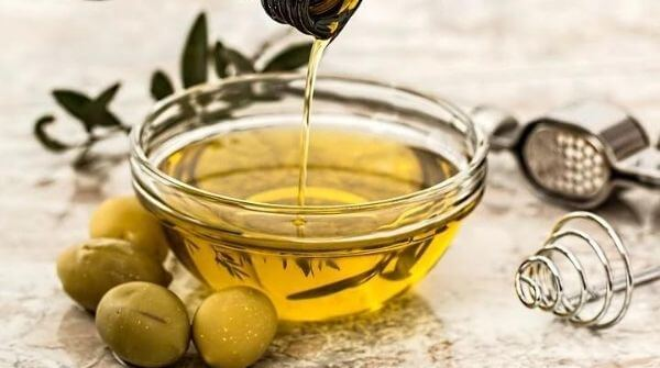 A bowl of olive massage oil with some olives around it.