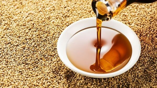 a bowl of sesame massage oil with  sesame oils around it.
